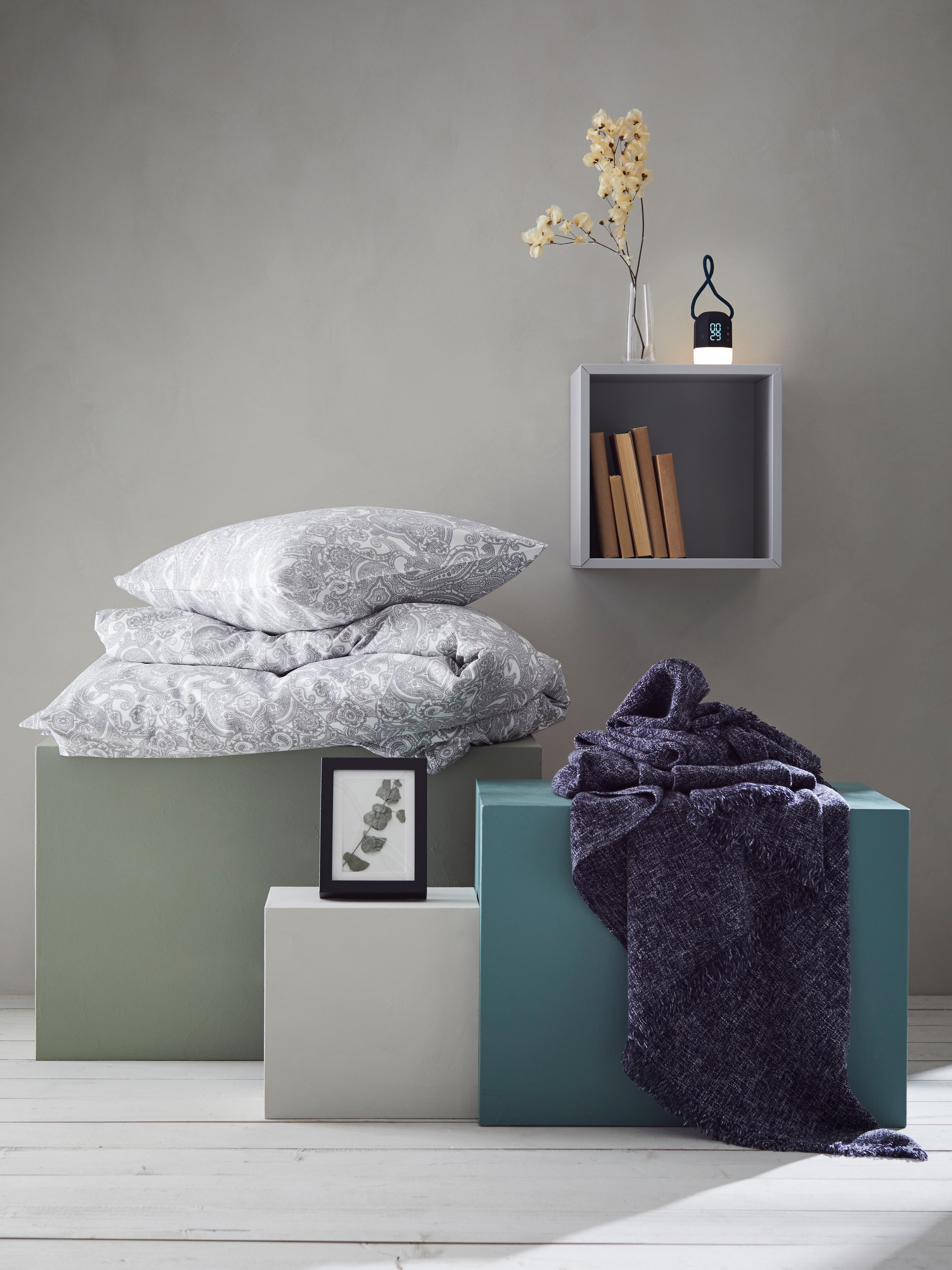 JÄTTEVALLMO set posteljine paisley uzorka, INDIRA lagana deka, RIBBA okvir za slike na postoljima te FNURRA budilica na polici.