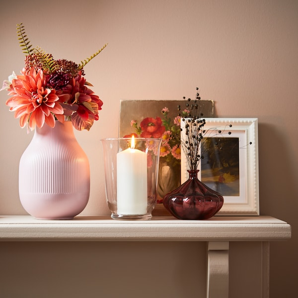 A ledge with a candle, picture frames and a pink vase filled with pink flowers