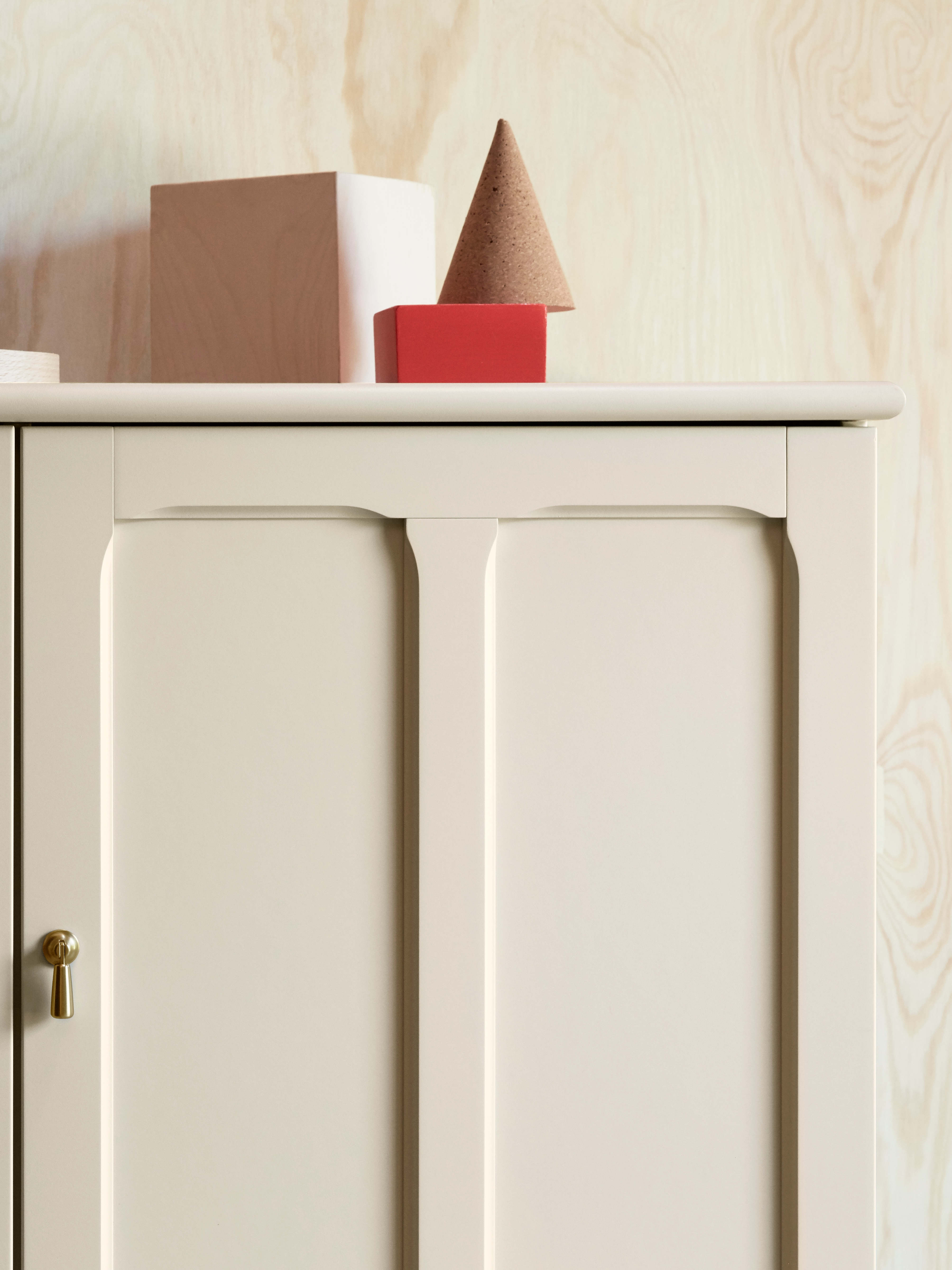 A close-up of the top right corner of a light beige LOMMARP cabinet with inset panels and champagne colour drop handles.