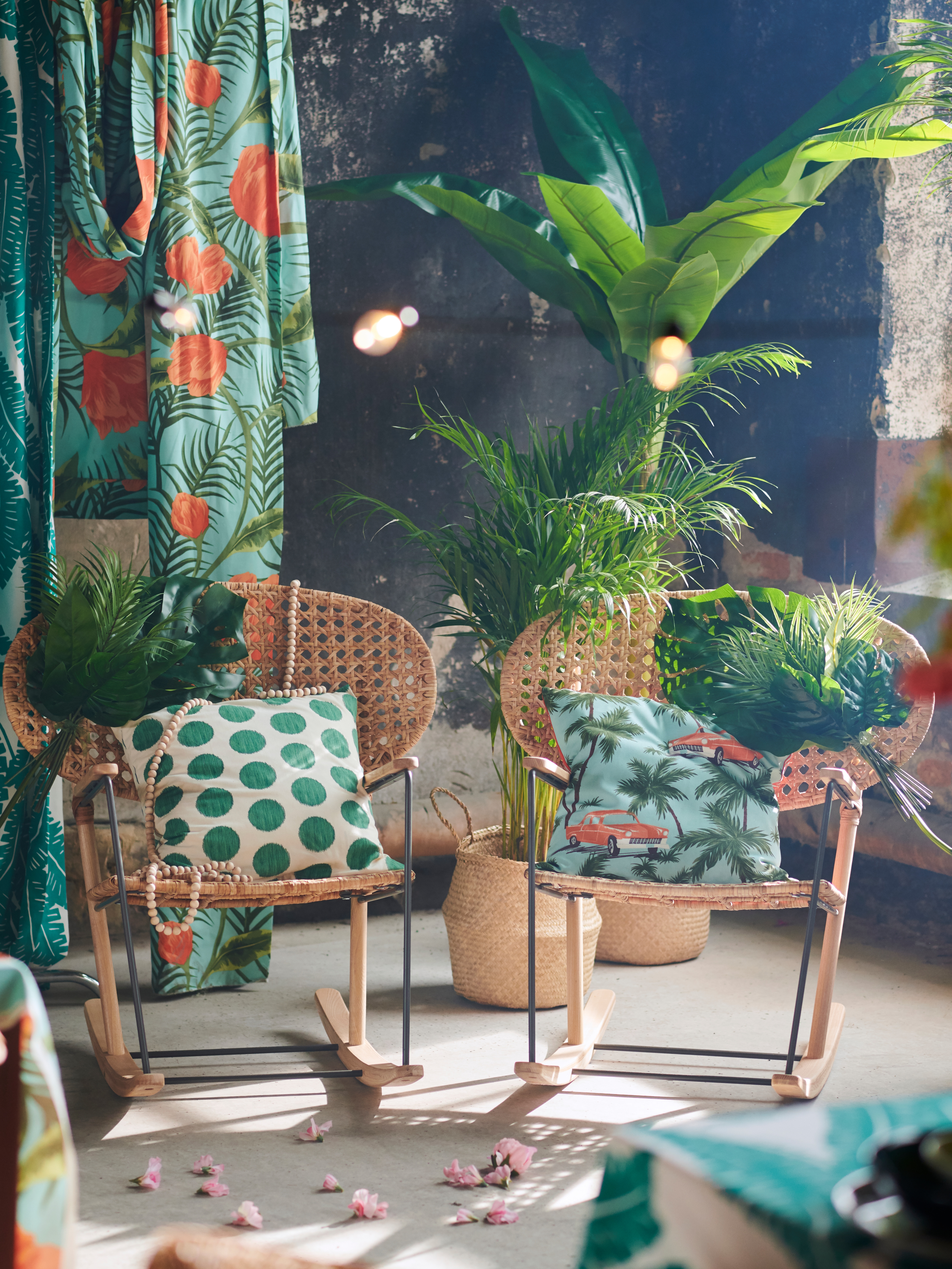 Two GRÖNADAL rocking chairs decorated with ÅSATILDA and SOMMAR 2020 cushions, surrounded by plants and SOMMAR 2020 fabric.
