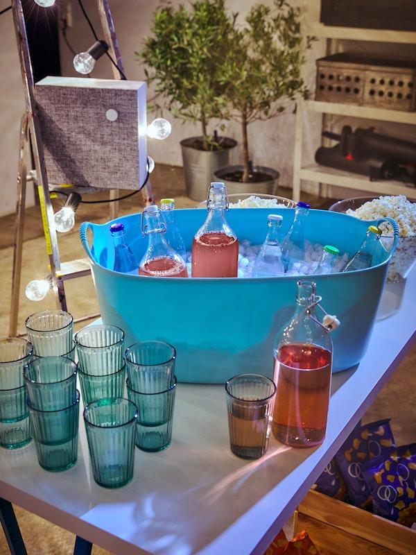 Un panier à linge souple TORKIS bleu rempli de glaçons et de bouteilles KORKEN.