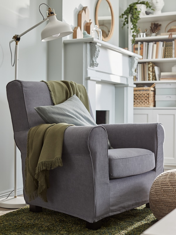 A grey armchair with a moss green throw and grey cushion, a white reading lamp, a green carpet and a brown pouffe.