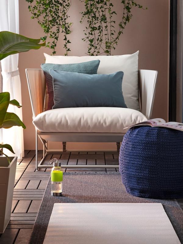Ein HAVSTEN Sessel und graue Kissen auf einem Bodenrost, auf dem ein Teppich liegt