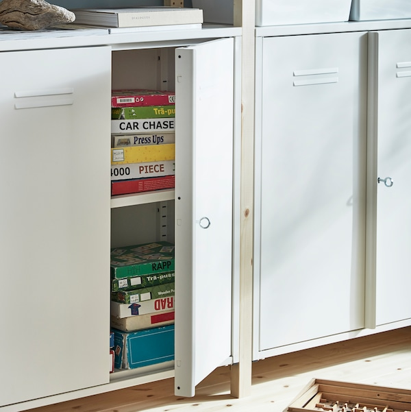Two steel IVAR cabinets stand against a wall. One has an open door and there are games and puzzles inside the cabinet.