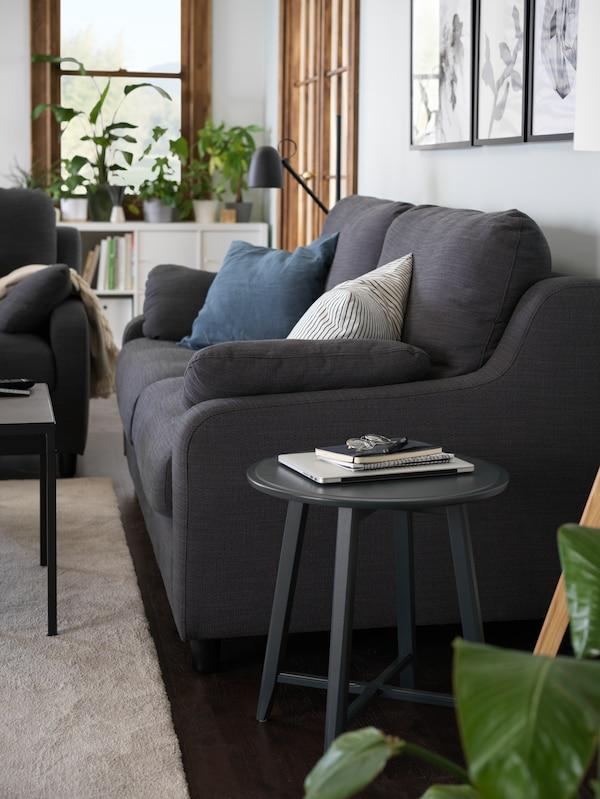 A dark blue-green colour KRAGSTA nesting table next to a VINLIDEN three-seat sofa.