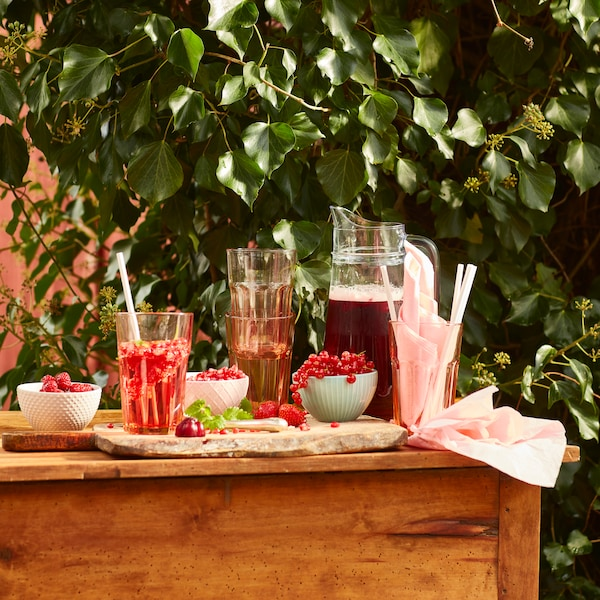 An outdoor table bearing a pitcher filled with red juice, bowls of berries, and tall glasses.