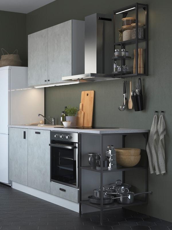 ENHET konyha szürke előlapokkal és antracit keretekkel, egy mohazöld helyiségben, edényekkel és serpenyőkkel, nyitott tárolókban.