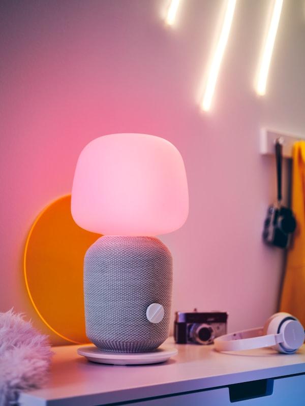 Lampa stołowa SYMFONISK z wbudowanym głośnikiem Wi-Fi, żółtą tacą, ze słuchawkami i z aparatem. Całość na blacie komody.