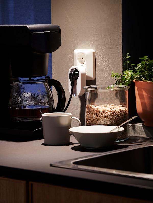 Eine Kaffeemaschine, die über eine Steuereinheit mit der Steckdose verbunden ist. Daneben ein Becher, eine Schüssel und Müsli in einer Glasdose.