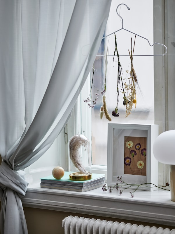 Drying flowers tied to a STAJLIG hanger suspended by a window. A VÄSTANHED frame and a BEGÅVNING dome stand on the sill.