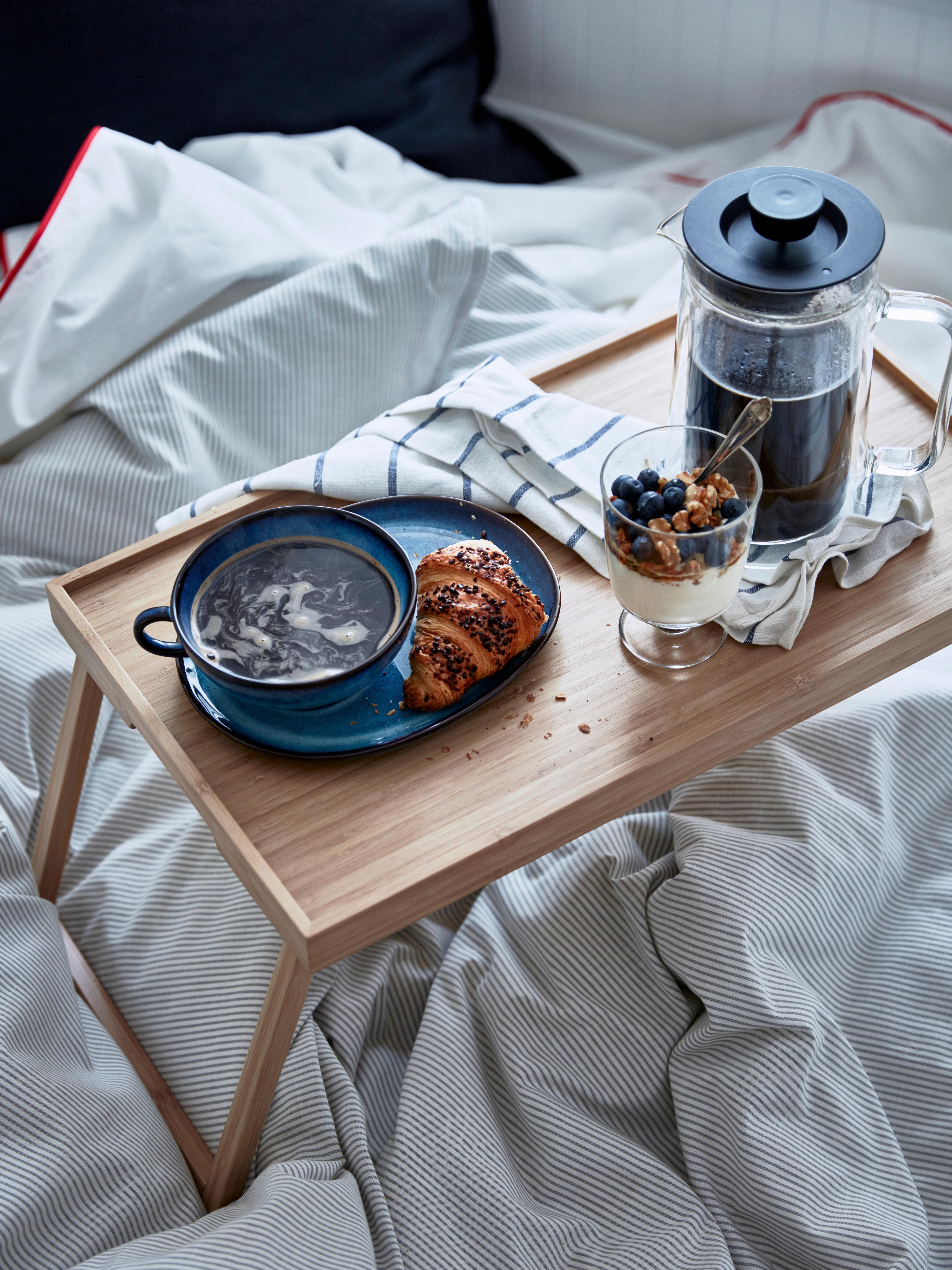 RESGODS poslužavnik postavljen na bijelu plahtu s plavim prugama. Poslužavnik od bambusa pun je potrepština za doručak.