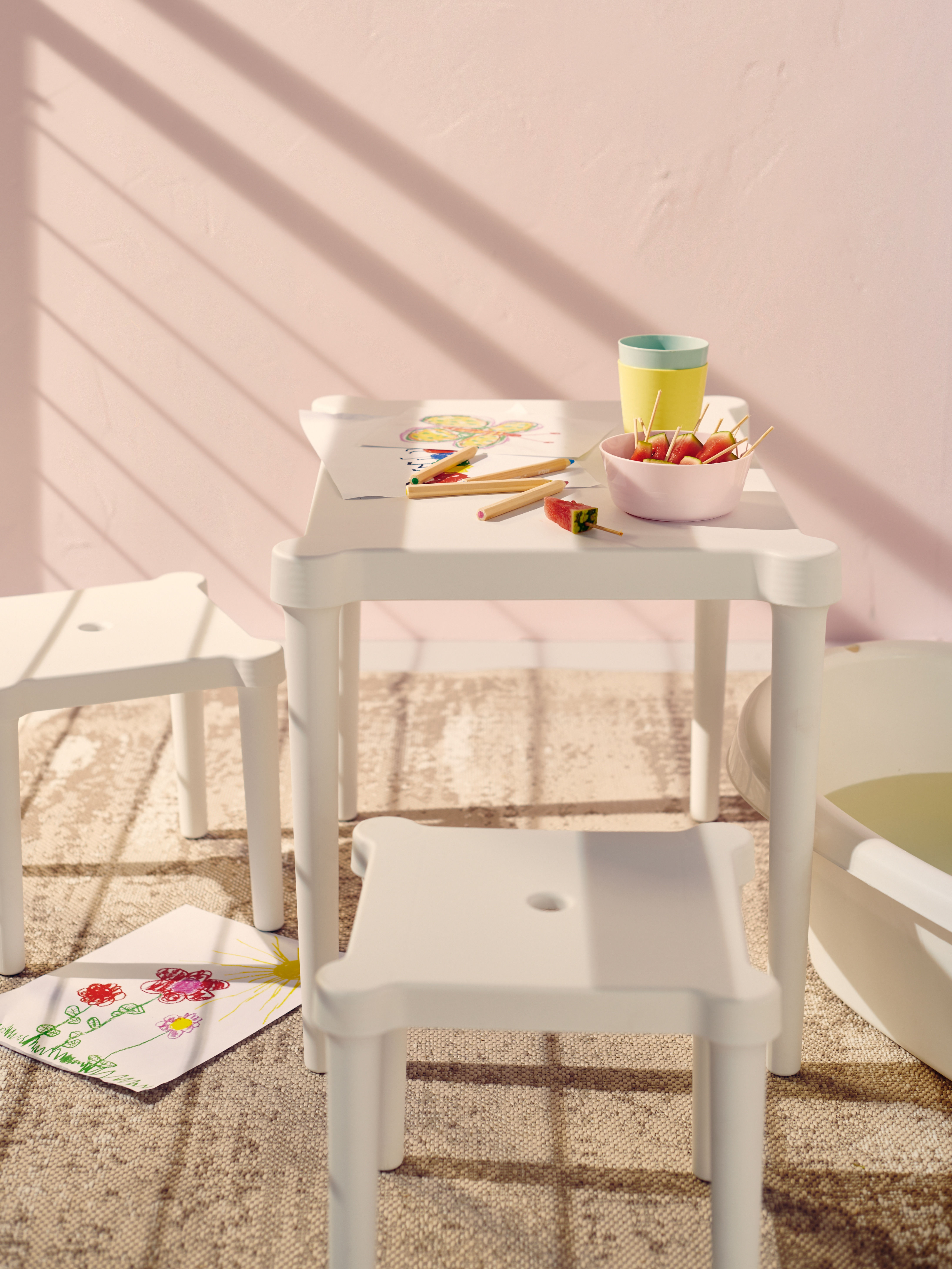 A white UTTER children's table with two stools creates an activity corner for the kids on a balcony with light pink walls.
