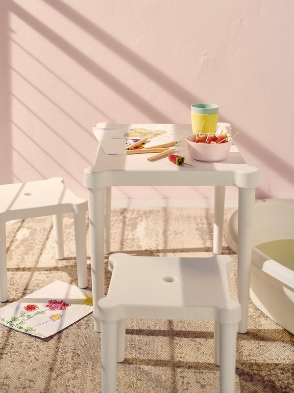 Bílý dětský stolek a 2 stoličky UTTER tvoří dětský koutek na balkoně se světle růžovými stěnami.
