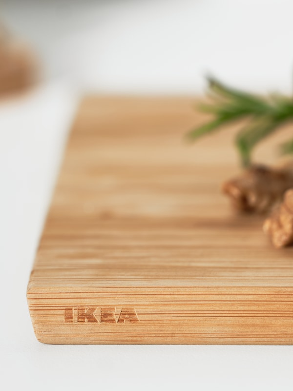 The side of an APTITLIG chopping board with the IKEA logo on it, with nuts and pineapple leaves on top.