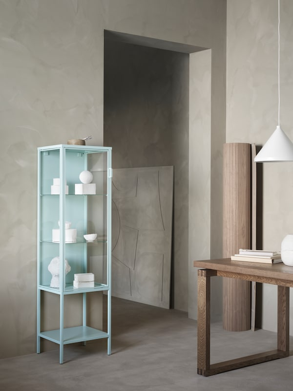 The turquoise RUDSTA glass-door cabinet filled with white ornaments in a minimal, neutral space.