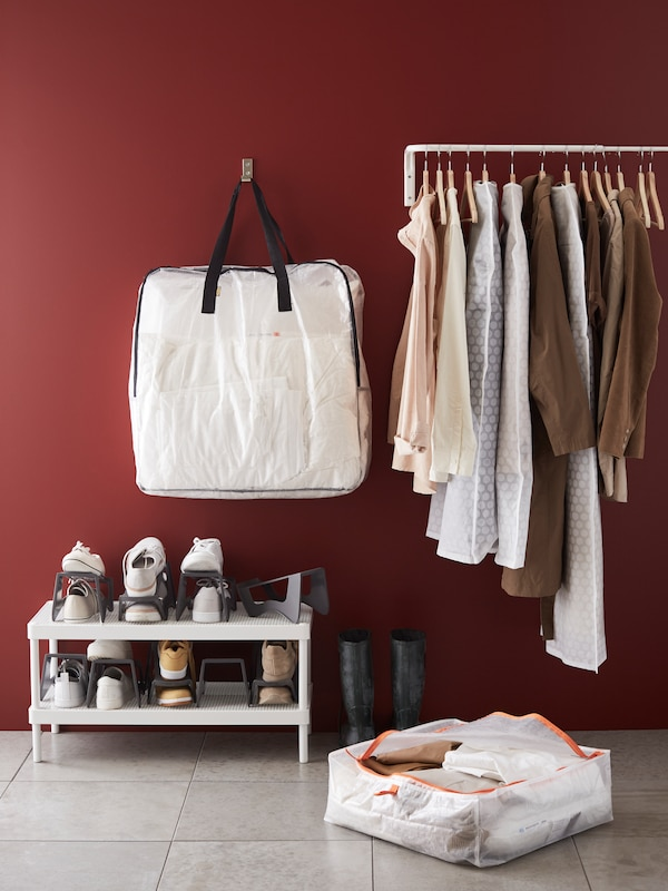 A hanging rail with some of the clothes in a PLURIG clothes cover, beside a DIMPA storage bag, and a MACKAPÄR shoe rack.
