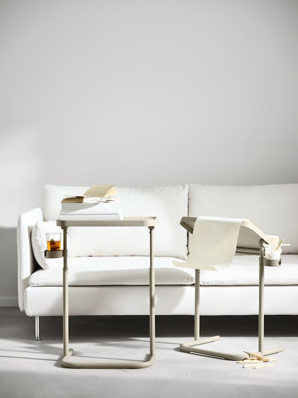 Two beige BJÖRKÅSEN laptop stands in front of a white sofa. One holds a pile of books, the other has a roll of paper on it.