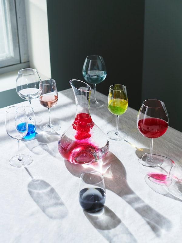 Several glasses filled with colourful drinks, placed on a white table.