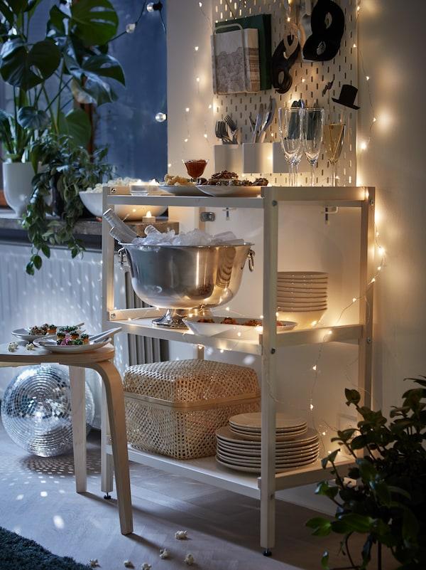Fehér EKENABBEN nyitott polcos elemet látunk, polcain tálak, poharak és egy pezsgőhűtő tál. Körülötte a falra LED világítófüzéreket aggattak.