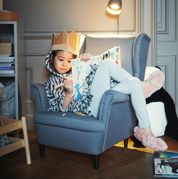 Dítě s hračkou sedí v šedém dětském křesle STRANDMON pod nástěnnou lampou a kreslí si.