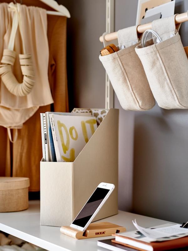 Egy fehér polcon álló bézs TJENA irattartó van előttünk, mellette egy bambusz telefontartóban tárolt mobiltelefont és függő textiltárolókat látunk.