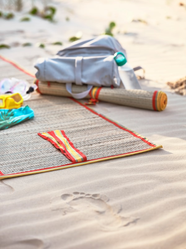 A woven beach mat with yellow and orange trimmings lying on sand. A light grey backpack lies next to it.