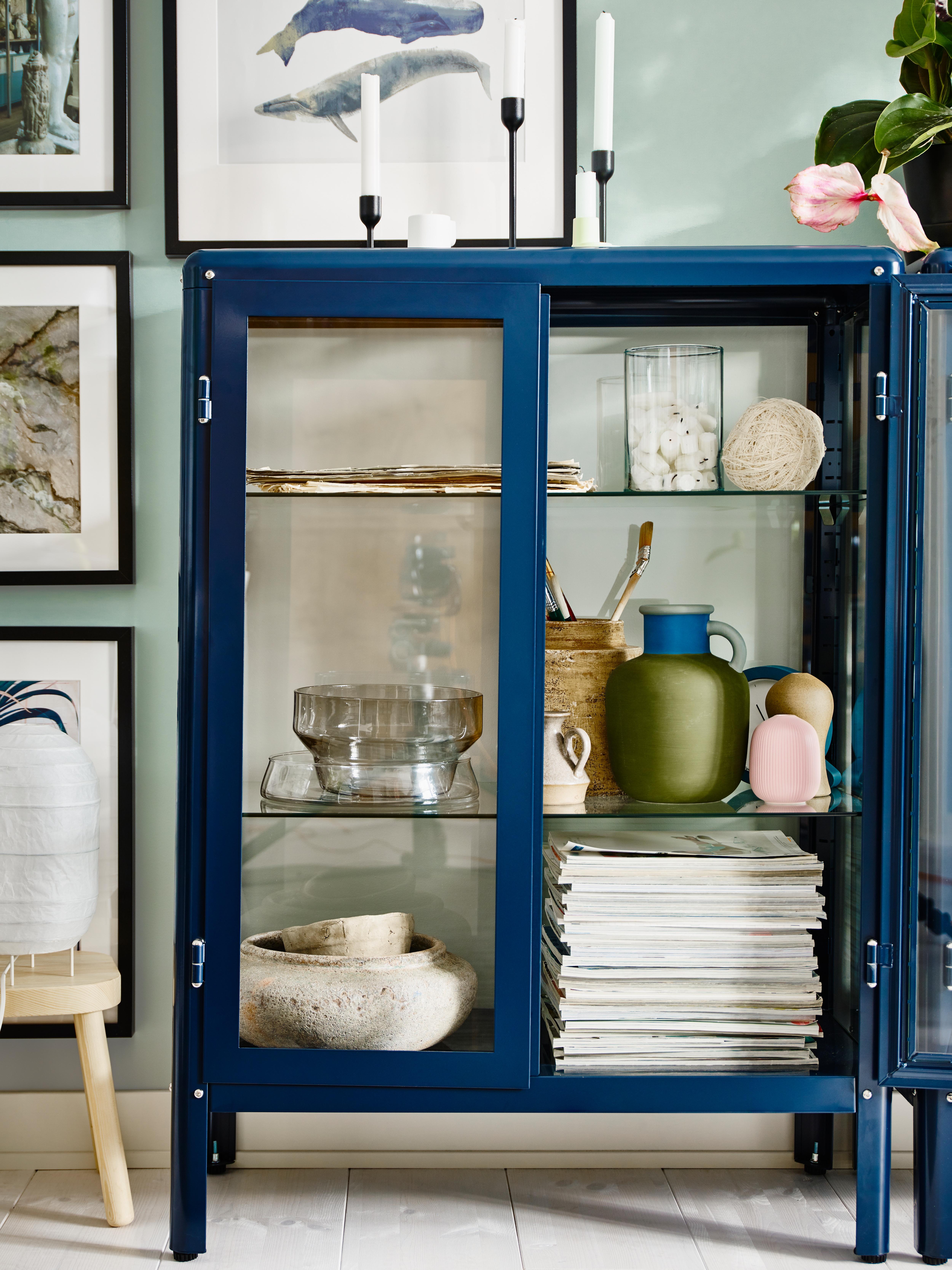 Crno-plava FABRIKÖR vitrina stoji pored uokvirenih slika na zidu i u njoj su časopisi, vaze i keramika.