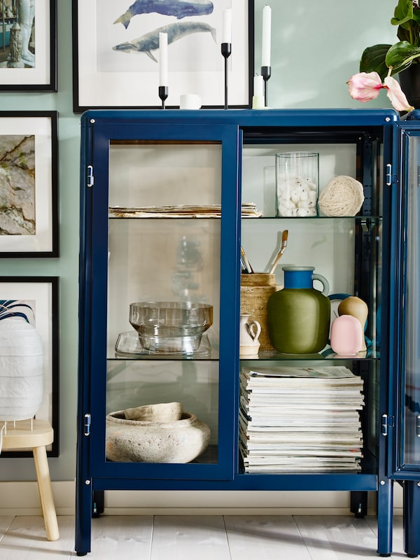 A black-blue FABRIKÖR glass-door cabinet stands by framed pictures on wall and holds magazines, vases and pottery.