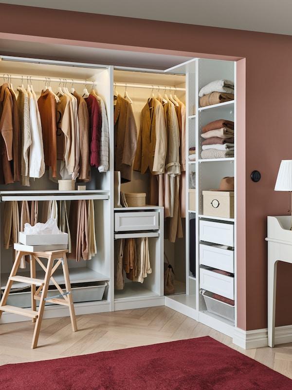En åben PAX hjørnegarderobeløsning med tøj hængende på garderobestænger, skuffer, hylder, buksebøjler og netkurve.