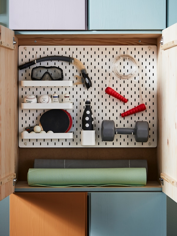 A white IKEA SKÅDIS pegboard combination shown inside an IVAR storage unit with sports equipment attached.