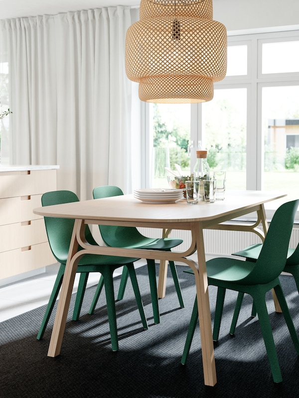 Et spisebord, en loftlampe og køkkenskuffefronter af bambus, grønne stole, et mørkegråt tæppe og hvide gardiner.