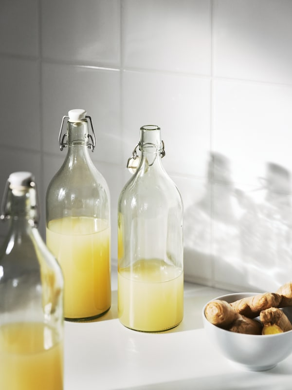Three KORKEN clear glass bottles with stopper filled with different amounts of orange juice beside a bowl of ginger.