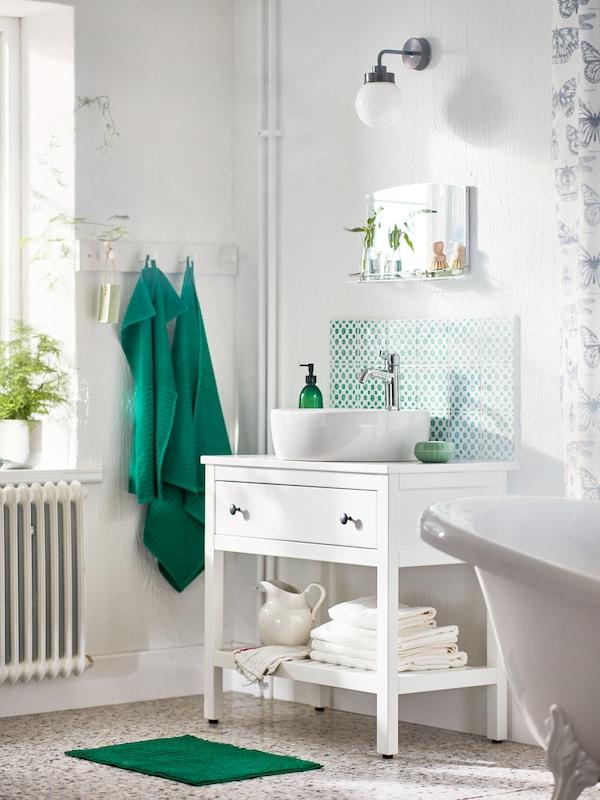 Egy HEMNES/TÖRNVIKEN nyitott mosdószekrény áll egy fürdőszoba sarkában, mellette néhány sötétzöld törülköző lóg akasztókról.