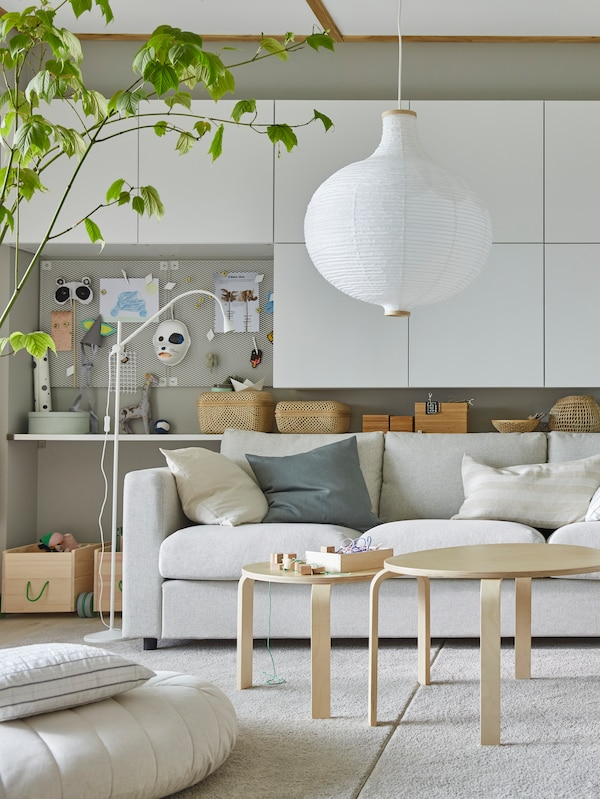 Part of a living room with white BESTÅ storage on a wall behind a beige VIMLE sofa and two birch veneer coffee tables.