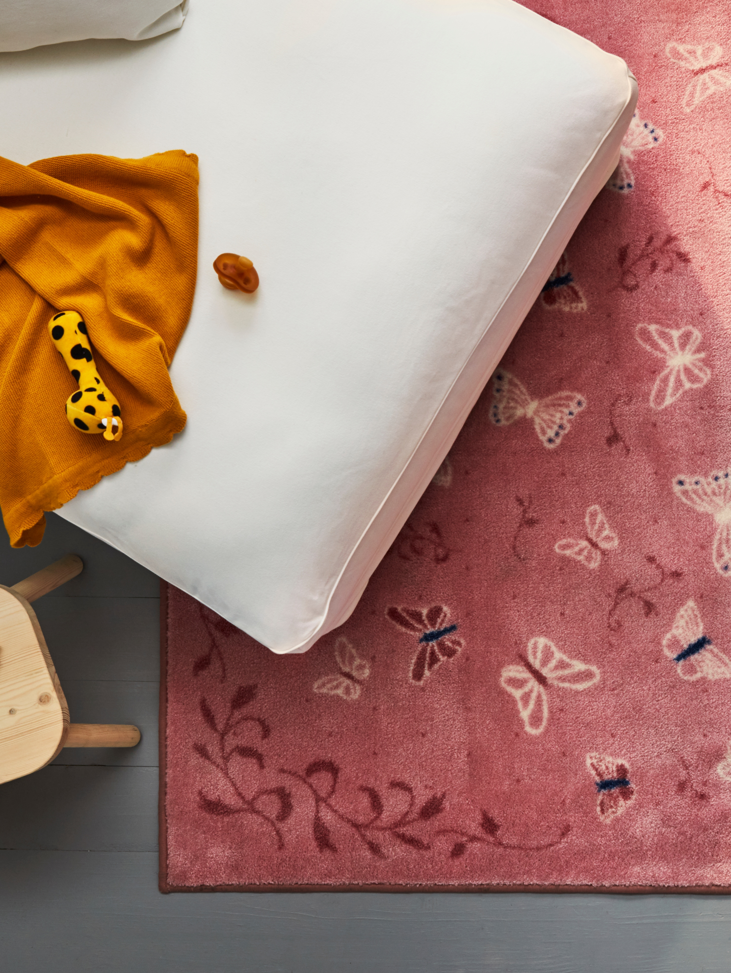 An aerial view of a SÅNGLÄRKA low pile rug in butterfly/pink that is partially under a chaise longue with a rattle on top.