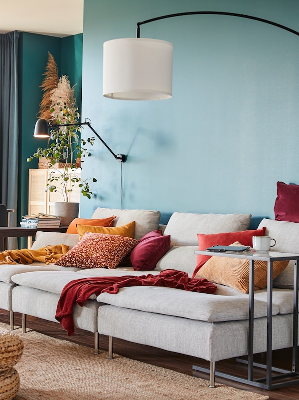 Vardagsrum som möblerats inför våren med VIMLE soffa, RÖDASK kuddfodral och SNÖBYAR lampa på ett VITTSJÖ bord.