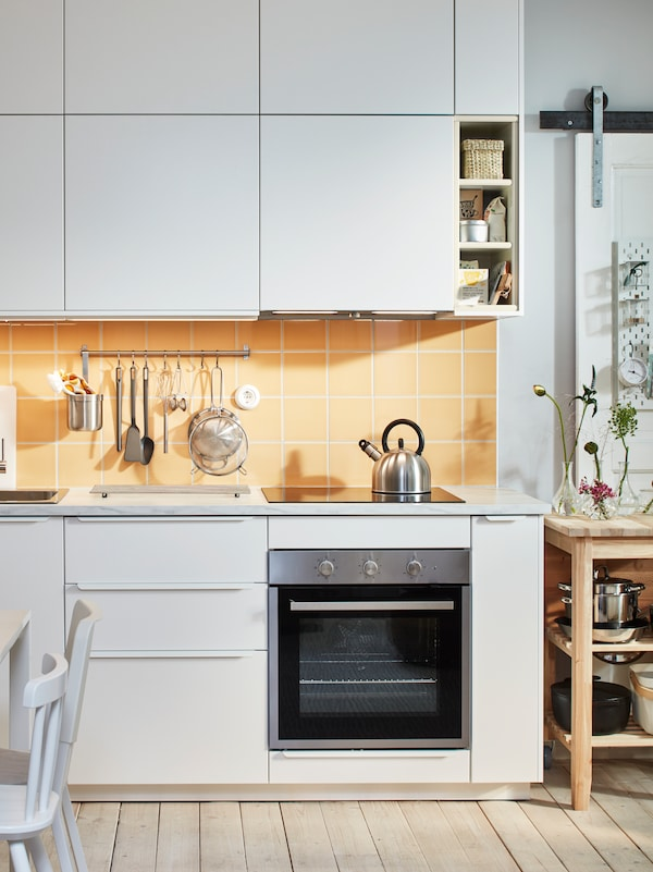 Bijela kuhinja s bijelim podnim elementima i bijelim zidnim elementima, žutim pločicama, pećnicom i drvenim kuhinjskim otokom.
