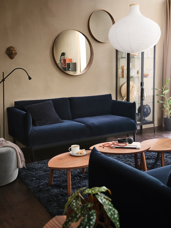 Két egymással szemben álló ÄPPLARYD kanapé egy nappaliban, közöttük egy sor dohányzóasztal, rajta egy csésze és egy laptop.