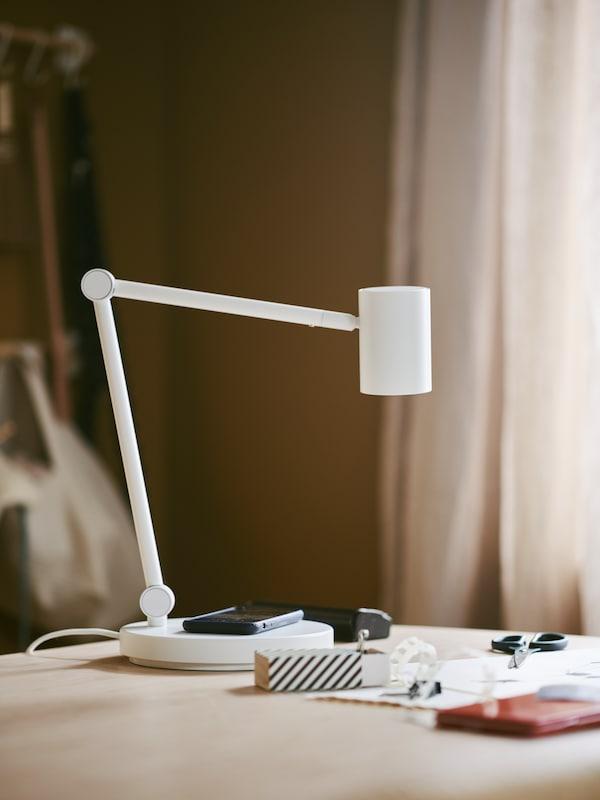 Egy asztalon álló NYMÅNE vezeték nélküli töltőjű íróasztallámpa alapján mobiltelefon fekszik.