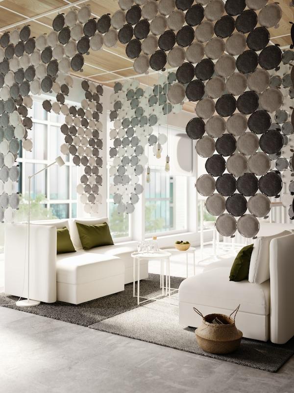 Accogliente area conversazione con divani componibili bianchi e pannelli fonoassorbenti grigio chiaro e grigio scuro appesi al soffitto.
