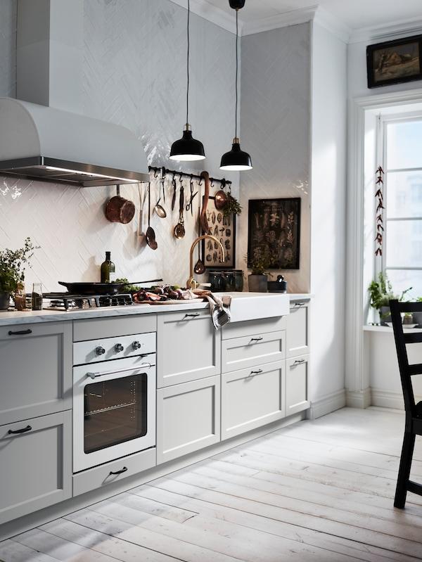 BODBYN БУДБІН кремово-біла кухня з продуктами на стільниці, на MATMÄSSIG МАТМЕССІГ газовій плиті стоїть сковорідка, на стелі – два чорні RANARP РАНАРП підвісні світильники.