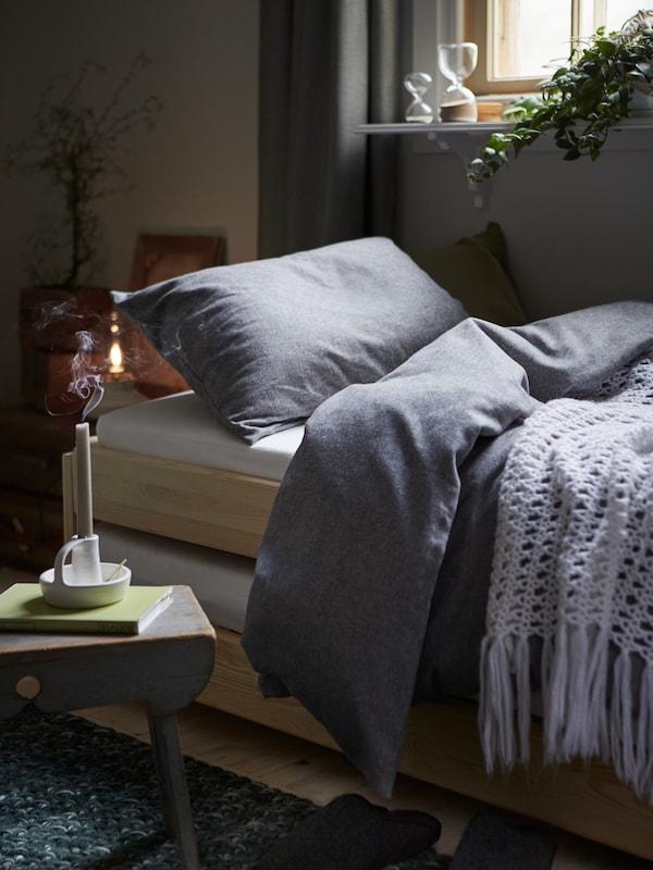 VÄSTKUSTROS-pussilakanasetti makuuhuoneessa, sammutettu kynttilä etualalla