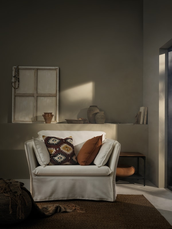 Koutek s příjemným osvětlením a texturovaným kobercem, 1,5místným křeslem BACKSÄLEN doplněným polštáři se zemitými a hřejivými vzory.