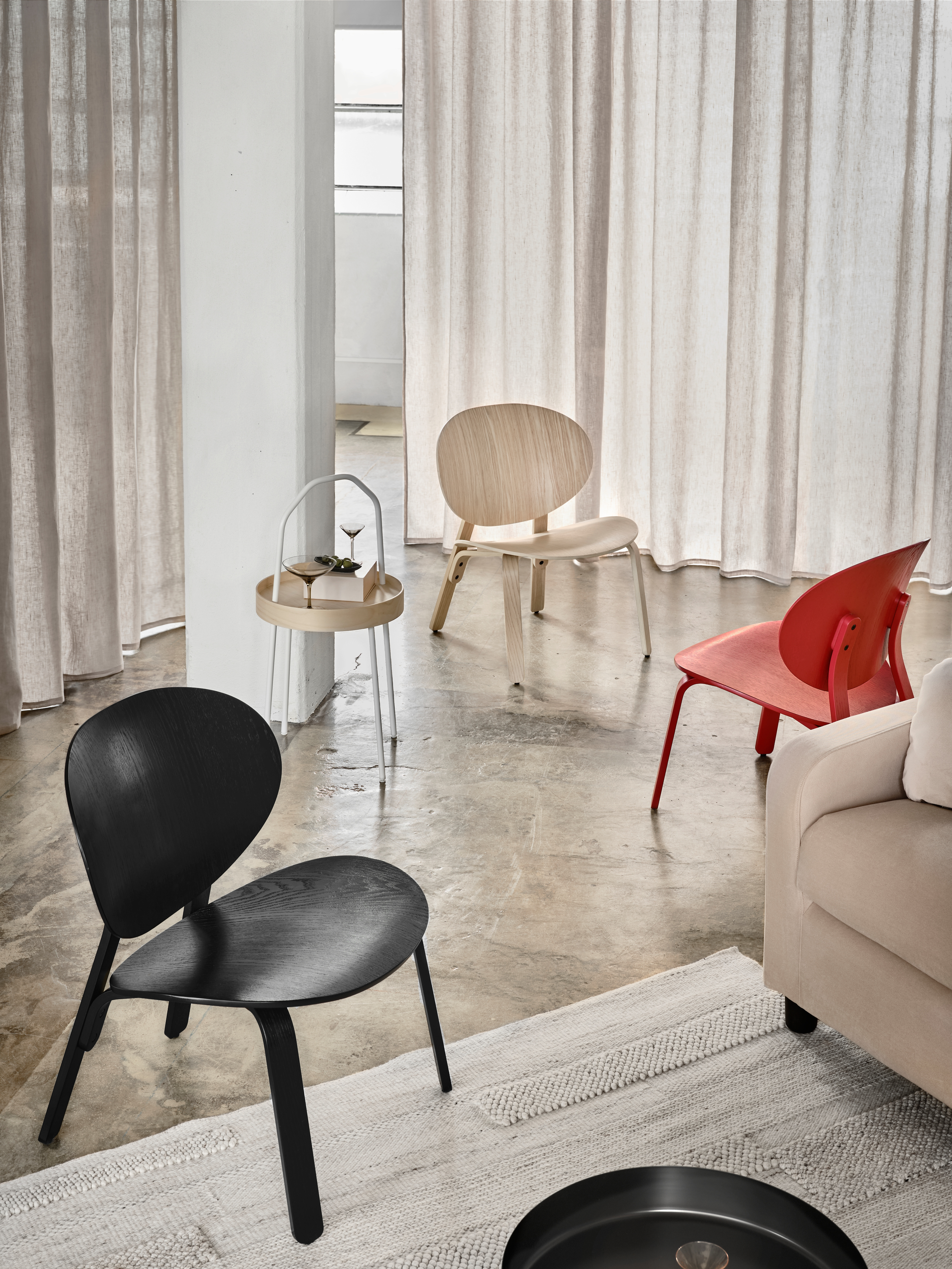Three FRÖSET chairs in white, red and black stained oak veneer standing in a relaxed way in connection to a sofa.