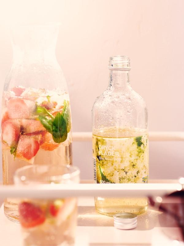Otwarta butelka syropu z bzu DRYCK FLÄDER ustawiona obok karafki VARDAGEN z wodą z truskawkami i miętą.