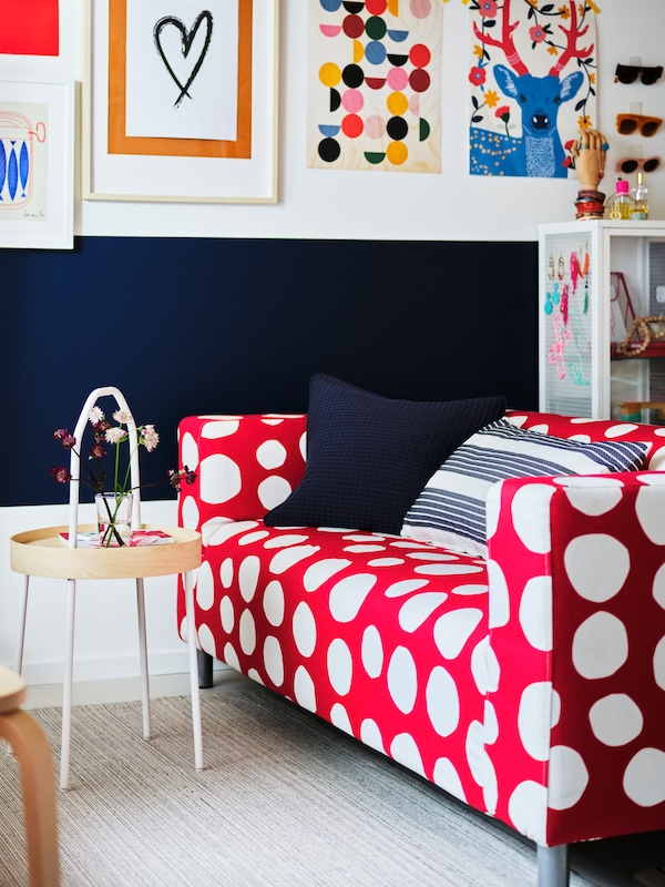 By a blue and white wall filled with art stand a red-and-white, polka-dot KLIPPAN two-seat sofa and a BURVIK side table.