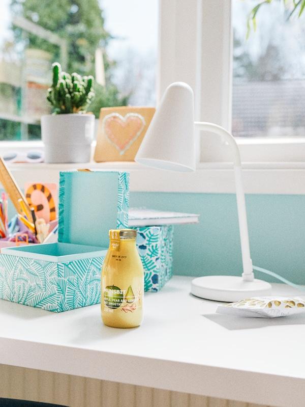 Un smoothie de ovăz MUNSBIT așezat pe un birou, în fața unei ferestre cu cutii de depozitare, instrumente de scris și o lampă de lucru FUBBLA de culoare albă.