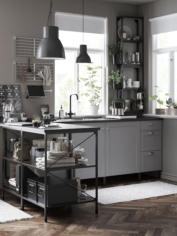 A kitchen with black frames and grey cabinets, two black pendant lamps, boxes, linen and glass jars on open storage.