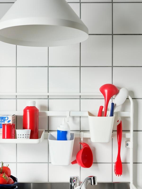 Bílé háčky, nádoby a police SUNNERSTA s červeným, modrým a bílým kuchyňským náčiním zavěšeným na minikuchyňské tyči SUNNERSTA.