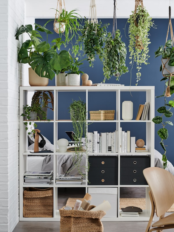 White KALLAX shelving unit with two black PALLRA mini chests with three drawers, plants, books and jute TJILLEVIPS basket.